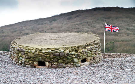 bristol channel: World War Two Pillbox on the Bristol Channel coast at Porlock Weir, Somerset ,UK. Built on the pebble beach and camouflaged with pebbles, after seventy years it is subsided and half buried but otherwise intact. Stock Photo