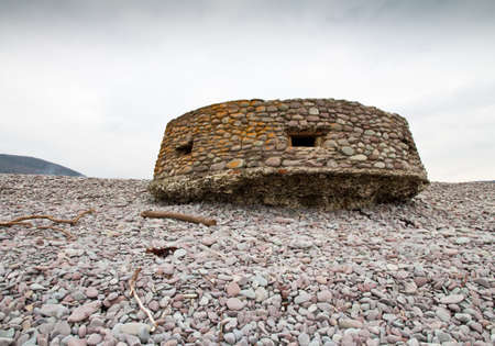 seventy two: World War Two Pillbox on the Bristol Channel coast at Bossington beach, Somerset ,UK. Built on the pebble beach and camouflaged with pebbles, after seventy years it is undercut but otherwise intact. Stock Photo