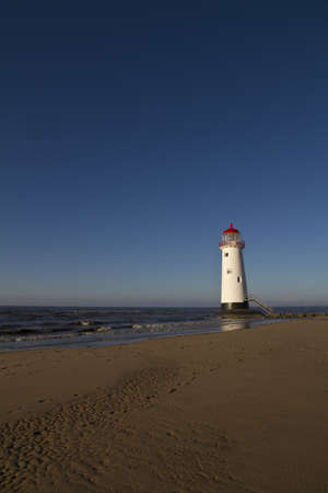 Point of Ayr Lighthouse, Wales UK  with an incoming tide at sunset photo