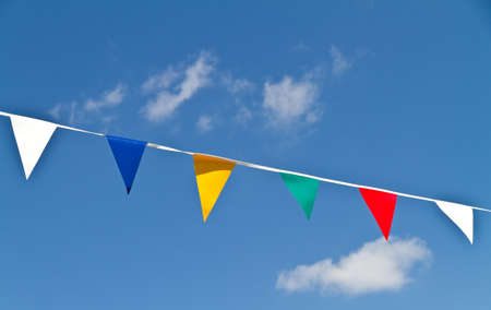 Brightly coloured bunting against a blue sky with fluffy clouds Stok Fotoğraf