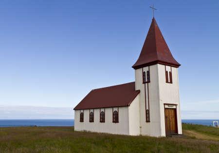 Remote Icelalandic Evangelisch-Lutherische Kirche an der Küste. Typische kleine einfache Struktur der isländischen Kirchen