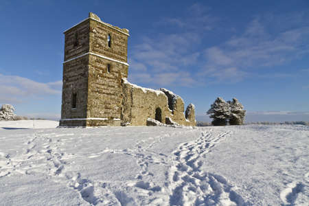 wiped out: The ruins of Knowlton Church in Dorset, UK covered in snow in winter. Knowlton church is situated within a bronze age burial mound and symbolises the transition from paganism to Christianity. The village of Knowlton was wiped out by the Black Death