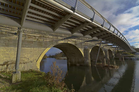 HDR image of an old road bridge with new foot bridge spanning the river Stour at Wimborne, Dorset, UK photo