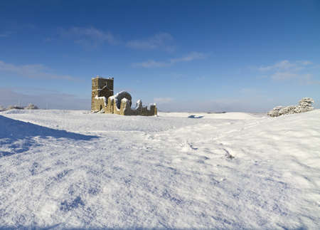 dorset: The ruins of Knowlton Church in Dorset, UK covered in snow in winter. Knowlton church is situated within a bronze age burial mound and symbolises the transition from paganism to Christianity. The village of Knowlton was wiped out by the Black Death