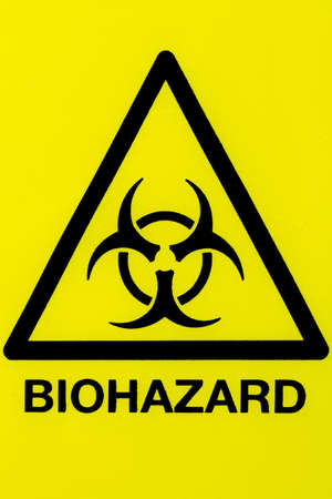 Close up of a biohazard symbol in a warning triangle black on yellow photo