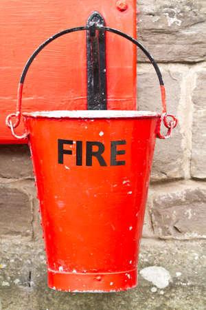 bombero de rojo: Solo el fuego un poco maltratadas cubo Foto de archivo