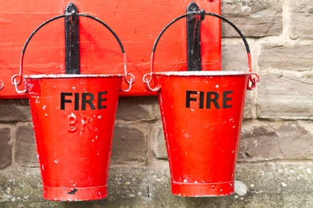 building on fire: Two slightly battered hanging fire buckets Editorial