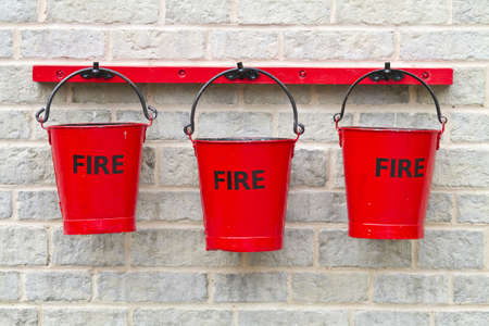 Three fire buckets hanging on a wall photo