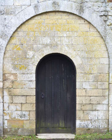 Mysterious old black wooden arched door set in a stone wall photo