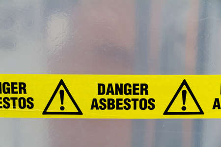Danger Asbestos yellow warning tape close up Stock Photo