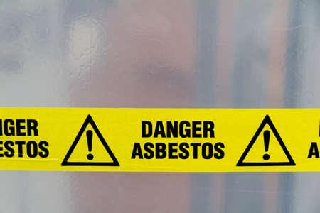 Danger Asbestos yellow warning tape close up photo