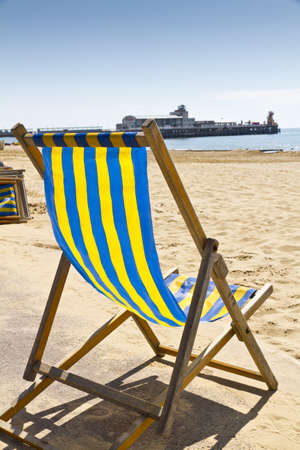 Single deck chair on the beach at Bournemouth, Dorset,UK with Bournemouth pier in the background
