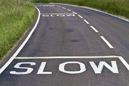 slow: Three warning signs to slow down painted on a curving road