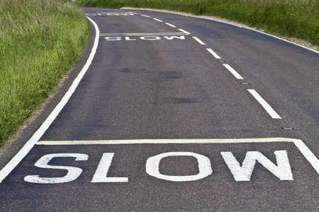 grass verge: Tre segnali di avvertimento per rallentare dipinto su una strada curva