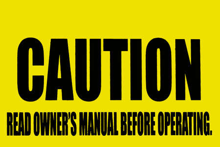 Caution Sign advising read owners manual before operating, black writing on yellow background