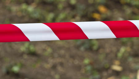 Red and white warning tape stretched across a blurred background Stock Photo - 16425020
