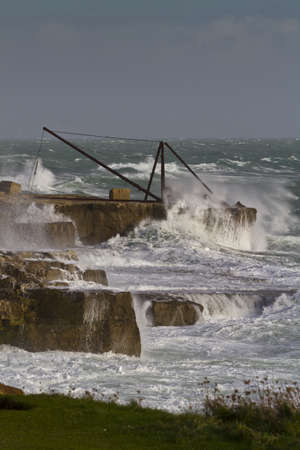 Storm waves breaking over a stone quarry crane, Portland Bill, Dorset,UK photo