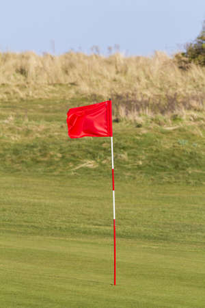 Red golf flag on a seaside links course in the UK Stok Fotoğraf