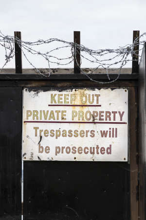 Private property, keep out trespassers will be prosecuted warning sign wit barbed wire photo
