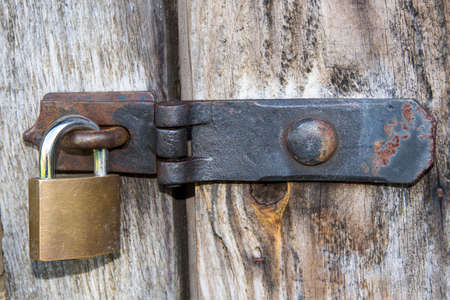 Close up of padlock and old metal hasp and staple on an old wooden door photo