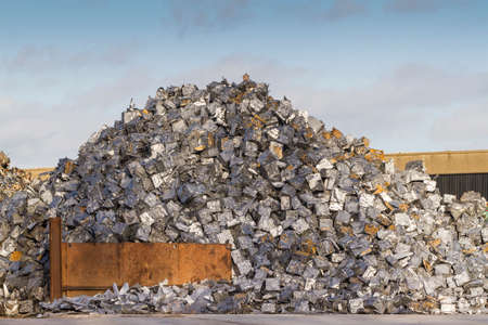 Scrap yard with pile of cars crushed into small cubes photo