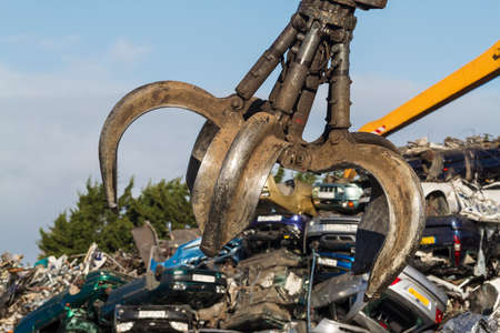junk yard: Close up of a Crane grab in a Scrapyard swinging above scrap cars