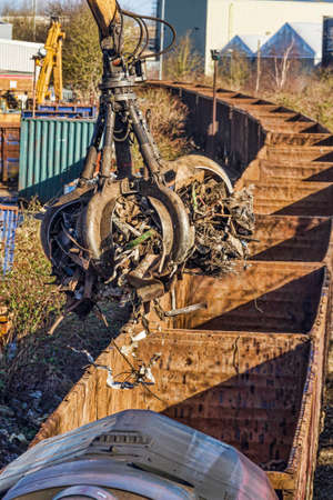 discarded metal: Grab crane loading scrap metal onto a train Stock Photo