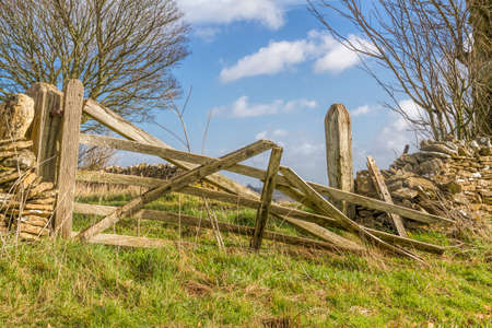 drystone: Broken old farm gate with drystone wall, in the Cotswolds,Gloucester, England Stock Photo