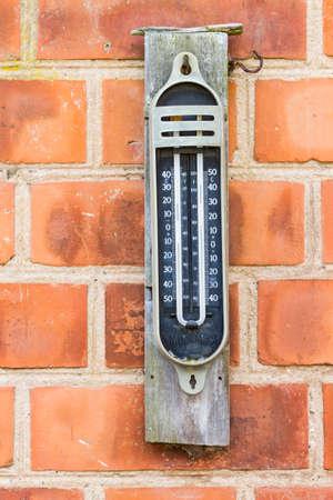 maximum: Old styly analog maximum minimum mercury thermometer ona brick wall