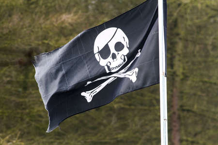 Skull and cross bones or pirate flag, flying in the wind photo