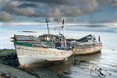 Three derelict fishing trawlers hauled up and rotting in a sea estuary