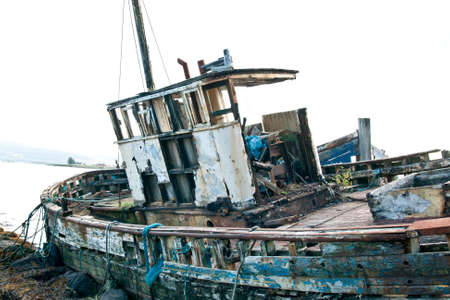 fishing industry: Derelict fishing trawler hauled up and rotting in a sea estuary Stock Photo
