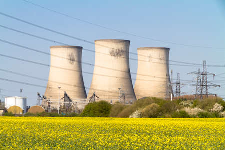 coal fired: Three electricity power station towers viewed across a field of rapeseed flowers