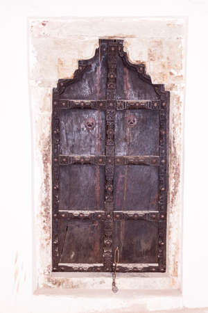 white washed: Ancient elaborately decorated Indian wooden door set in a white washed wall Stock Photo