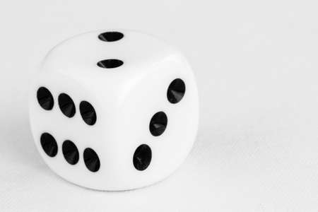 Macro of single Dice on a white cloth surface with shallow depth of field
