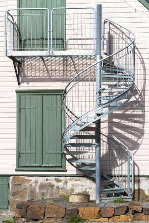 escape: External, metal, spiral staircase fire escape Stock Photo