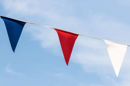 sunlit: Close up of sunlit red white and blue triangular bunting against a blue sky