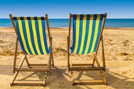 deck: Two blue and yellow deckchairs facing the sea across golden sand on a bright sunny day, Bournemouth, UK