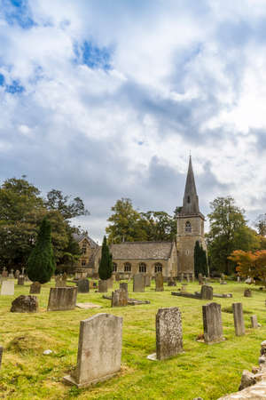 slaughter: Sunlit picturesque church  and graveyard, Lower Slaughter, Gloucestershire,UK Stock Photo