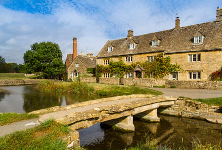 cotswold: Stream running through the picturesque Cotswold village of Lower Slaughter, Gloucestershire, England, with footbridge and mill