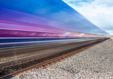 train station: Close up of train speeding through English countryside on bright sunny day with extended exposure for extended   motion blur Stock Photo