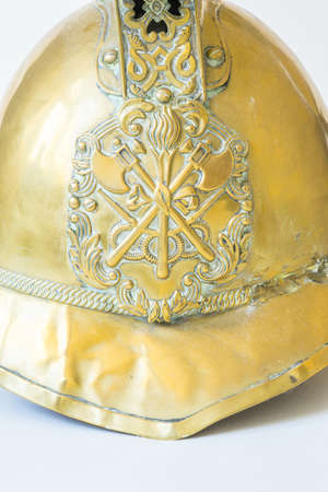 British Other Ranks Merryweather Brass Fire Helmet, used during the blitz, Second World War, with consequent damage. Close up of badge showing crossed axes,torch and hose pipes