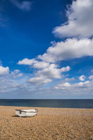 skiff: Single rowing boat ona shingle beach facing out to sea on a  bright sunny summers day