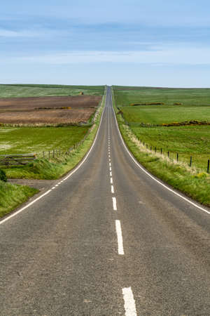 Long straight tarmac road with open fields, disappearing over far horizon, Island of Orkney, Scotland, UK