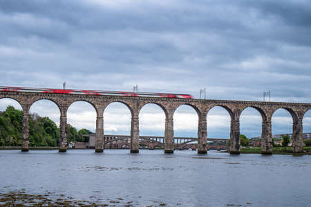 Motion blurred express train crossing the Royal Border Bridge Berwick upon Tweed, Northumbria England. Stock Photo