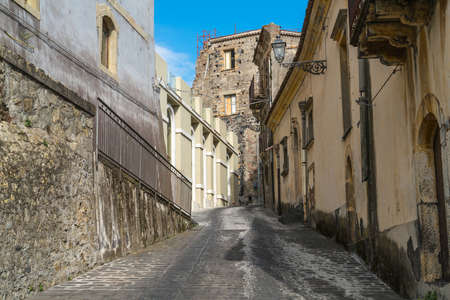 Steep street in Castiglione di Sicilia, Sicily, Italy with basalt cobbles and quaint old buildings on a sunny day Stock Photo