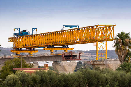 Motorway or autostrada bridge construction with large gantry crane lifting in road sections between pillars. Sicily, Italy