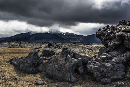 Dramatic Icelandic Lava Landscape near Herðubreið Volcano in the central Highlands. Weathered lava in foreground and mountains and stormy sky background Stock Photo