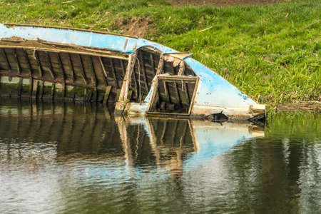 Close up of Half submerged boat wreck on the banks of a river