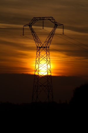 sunsetting behind an electricity pylon Stock Photo